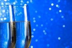 Paires de cannelures de champagne sur le fond clair bleu de bokeh Image stock