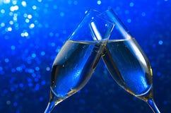 Paires de cannelures de champagne sur le fond clair bleu de bokeh Photos stock