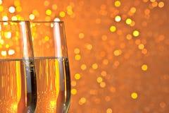 Paires de cannelures de champagne sur le fond de bokeh de lumière orange et jaune Images stock