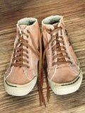 Paires de chaussure de gymnase à la mode sur le plan rapproché pris par fond en bois Image libre de droits