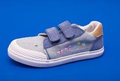 Paires de chaussures de bébé de denim de mode les pieds d'enfants en bas âge Badine des espadrilles sur le fond bleu Photographie stock