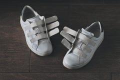 Paires de chaussures blanches et usées sur le Velcro Images stock
