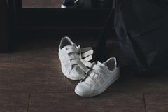 Paires de chaussures blanches sur le Velcro avec le sac à dos Photographie stock
