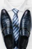 Paires de chaussures bleues classiques se tenant sur une chemise et un lien Mode du ` s d'hommes photographie stock
