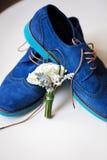 Paires de chaussures bleues de mariés élégants avec le boutonniere Photographie stock libre de droits