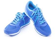Paires de chaussures bleues de sport sur le fond blanc Image libre de droits