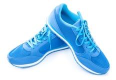 Paires de chaussures bleues de sport sur le fond blanc Images stock