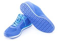 Paires de chaussures bleues de sport sur le fond blanc Photos libres de droits