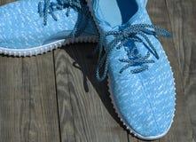 Paires de chaussures bleues de textile sur une surface en bois grise Images stock