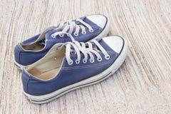Paires de chaussures bleues de toile sur le fond en bois, bleu sale s Photo stock