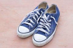 Paires de chaussures bleues de toile sur le fond en bois, bleu sale s avec l'espace de copie Photographie stock