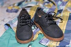 Paires de chaussures de bébé bleu-foncé sur le pantalon et la chemise à la cérémonie de baptême de baptême à la chapelle d'église Photo stock