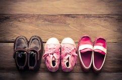 3 paires de chaussures de bébé ont aligné sur le fond en bois Photographie stock