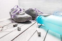 Paires de chaussures, de bouteille d'eau et d'écouteurs de sport sur le bois blanc Photographie stock