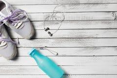 Paires de chaussures, de bouteille d'eau et d'écouteurs de sport sur le bois blanc Image stock