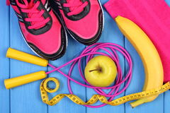 Paires de chaussures, de fruits frais et d'accessoires roses de sport pour la forme physique sur les conseils bleus Photographie stock
