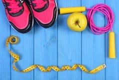Paires de chaussures de sport, de pomme fraîche et d'accessoires pour la forme physique sur les conseils bleus, l'espace de copie Photo libre de droits