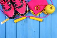 Paires de chaussures de sport, de pomme fraîche et d'accessoires pour la forme physique sur les conseils bleus, l'espace de copie Photographie stock libre de droits