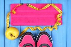 Paires de chaussures de sport, de pomme fraîche et d'accessoires pour la forme physique sur les conseils bleus, l'espace de copie Image libre de droits