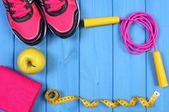 Paires de chaussures de sport, de pomme fraîche et d'accessoires pour la forme physique sur les conseils bleus, l'espace de copie Photo stock