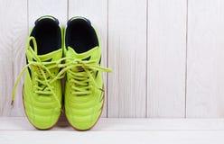 Paires de chaussures de sport sur un mur en bois blanc Photos libres de droits