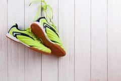 Paires de chaussures de sport sur un mur en bois blanc Photographie stock libre de droits