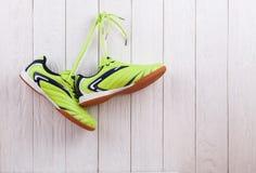 Paires de chaussures de sport sur un mur en bois blanc Images libres de droits