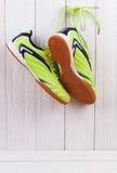 Paires de chaussures de sport sur un mur en bois blanc Photographie stock