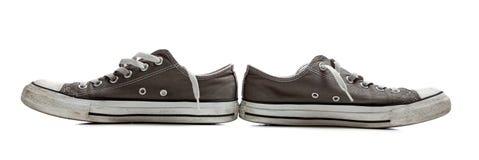 Paires de chaussures de tennis grises sur le blanc Images stock