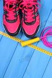 Paires de chaussures et d'accessoires roses de sport pour la forme physique sur les conseils bleus, l'espace de copie pour le tex Photographie stock