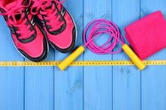 Paires de chaussures et d'accessoires roses de sport pour la forme physique sur les conseils bleus, l'espace de copie pour le tex Photos stock