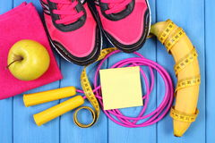 Paires de chaussures et de fruits frais roses de sport sur les panneaux bleus, l'espace de copie pour le texte sur la feuille de  Photo stock