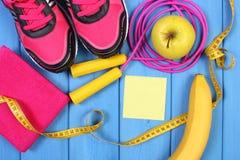 Paires de chaussures et de fruits frais roses de sport sur les panneaux bleus, l'espace de copie pour le texte sur la feuille de  Photo libre de droits