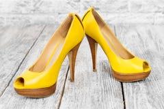 Paires de chaussures de femme sur un plancher en bois Thème de talons hauts, d'achats et de vente Image libre de droits