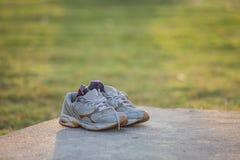 Paires de chaussures grises de sports sur le plancher de ciment en parc Photographie stock