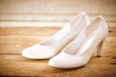 Paires de chaussures nuptiales blanches sur le plancher en bois rustique Image stock