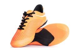 Paires de chaussures oranges de sport sur le fond blanc Image stock