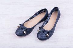 Paires de chaussures plates de ` bleu-foncé de dames sur le fond en bois blanc Photo stock