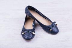 Paires de chaussures plates de ` bleu-foncé de dames sur le fond en bois blanc Photographie stock