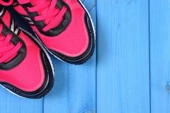 Paires de chaussures roses de sport sur les conseils bleus, l'espace de copie pour le texte Photographie stock