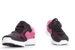 Paires de chaussures roses et noires de sport sur le fond blanc Images stock