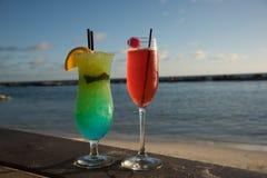 Paires de cocktails colorés sur la plage photos stock
