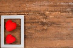 Paires de coeurs rouges dans le cadre blanc sur la table en bois de cru, vue supérieure fond de jour de valentines de saint photos stock