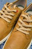 Paires de couleur bronzage, espadrilles en cuir sur des jeans fond, vue en gros plan Photographie stock libre de droits