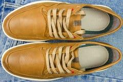 Paires de couleur bronzage, espadrilles en cuir sur des jeans fond, vue supérieure Images libres de droits