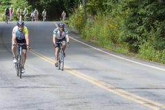 Paires de cyclistes sur la longue colline dans le défi de la Casserole-masse Images stock