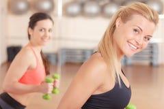 Paires de femmes faisant la forme physique de poids Images stock