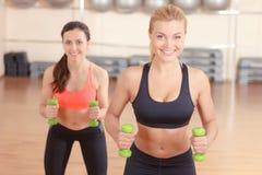 Paires de femmes faisant la forme physique de poids Photos stock
