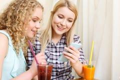Paires de femmes regardant le téléphone en café Images libres de droits