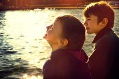 Paires de frères s'asseyant sur la promenade au coucher du soleil Photo libre de droits